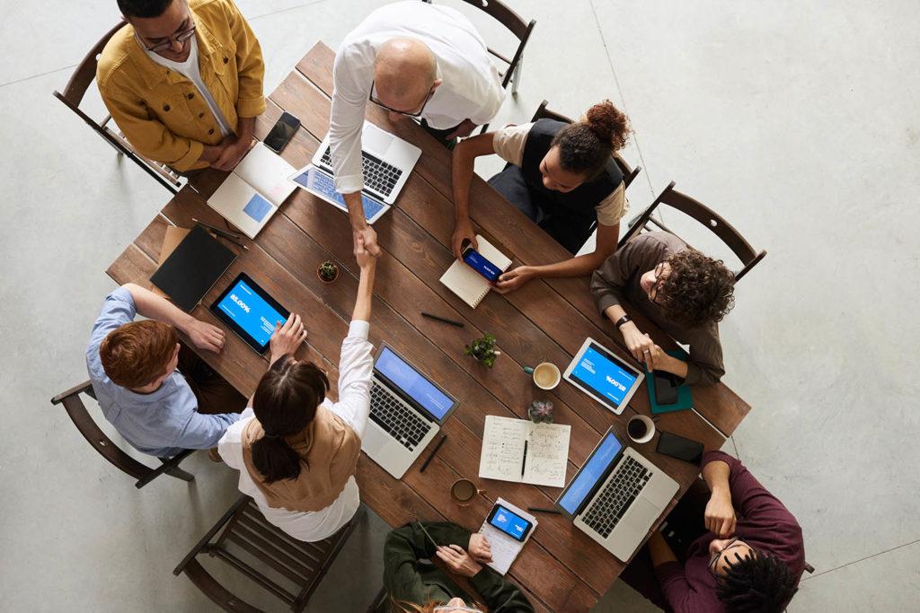 Wokół stołu - osoby z komputerami do pracy